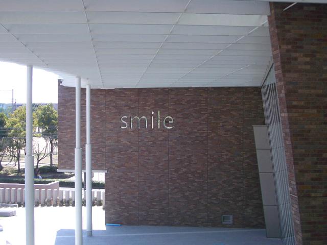 """畿央大学 /藤本由起夫 """"smile"""" / 記念ホール外壁"""